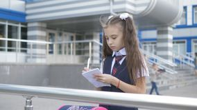 Student in school uniform near school building writes something in a notebook. stock video footage