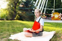 Student schoolgirl with pigtails in uniform holding books in her hands on a bright sunny day sitting on a blanket in the park royalty free stock photography