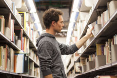 Student selecting a book in a library. Young male student selecting a book from a library shelf, high school Stock Images