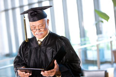 Student: Senior Adult Male Student Reading Diploma Stock Image