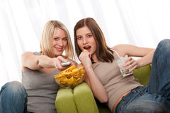 Student series - Two teenage girls watching TV. Two teenage girls watching TV and eating potato chips Royalty Free Stock Photography
