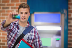 Student showing his card to camera at the atm Royalty Free Stock Photos