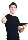 Student showing okey thumb. Male student showing okey thumb up holding a touch pad against white background Royalty Free Stock Photography