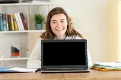Student showing to camera a blank laptop screen. Front view portrait of a happy student showing to camera a blank laptop screen stock photography