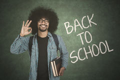 Student shows ok sign with back to school text. Male afro student showing ok sign while holding book with back to school text on chalkboard Stock Images