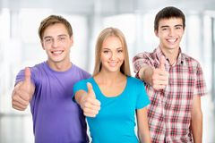 Student shows thumb up. Group of happy students giving the thumbs-up sign Stock Images