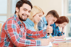 Student shows thumb up. Best time studying. Young smiling male student showing his thumb up sitting in class with his peers Stock Images