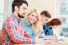 Student shows thumb up. Happy students. Young smiling blond female student showing thumb up sitting with her group mates at the desk Stock Image