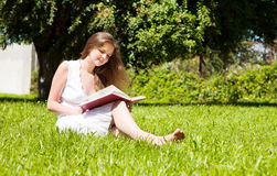 Student sit on lawn and reads textbook Royalty Free Stock Photo