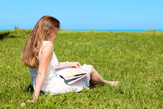 Student sit on lawn and reads textbook Stock Photos
