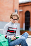 Student sits on bench and looking at Tablet-PC royalty free stock photography