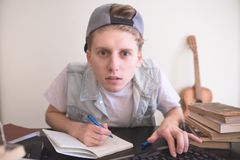 Student sits at a computer near the books, looks at the monitor and writes in a notebook stock image