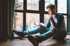 Student sits on the floor with laptop and reads something Stock Photography