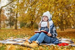 Student sits on a plaid in the park and reads a book stock photography