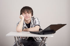 Student sits for a portable computer. Student bothered to learn, he sits at the table on which stands the computer Stock Images