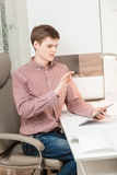 Student sitting behind desk and browsing with hand on tablet Royalty Free Stock Photo
