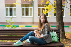 Student sitting on bench with book Stock Photo