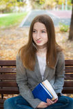 Student sitting on bench with headphones and book Stock Image