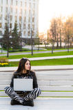 Student sitting on bench listening to music and using laptop against university campus looking away Stock Photos