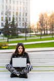 Student sitting on bench listening to music and using laptop against university campus looking away royalty free stock photography