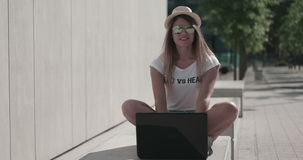 Student sitting on the bench using her laptop computer stock footage
