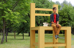 Teenage Boy Sitting on a Big Chair. Student sitting on a big chair in the park Royalty Free Stock Images