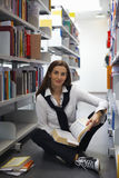 Student sitting between bookshelves reading Stock Image