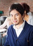 Student Sitting With Classmates In Background At. Portrait of confident male student sitting with classmates in background at classroom Royalty Free Stock Photos