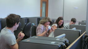 Student sitting at the computer and having fun with paper airplanes stock video footage
