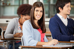 Student Sitting At Desk With Classmates In Royalty Free Stock Photo