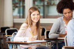 Student Sitting At Desk met binnen Klasgenoten royalty-vrije stock afbeelding
