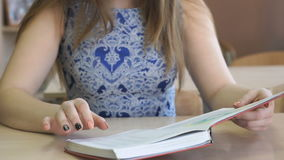 Student sitting at desk reads textbook indoors stock video