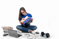 Student sitting down searching throw files. With books around isolated on white background Stock Images