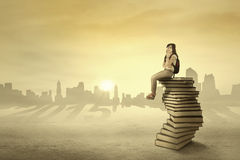 Student sitting and dreaming above books Stock Image