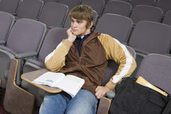 Student Sitting In Empty Classroom. Young male student sitting with book in an empty classroom Stock Photography