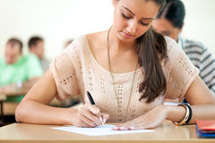 Student sitting for exam. Student girl sitting for exam in a classroom Royalty Free Stock Images