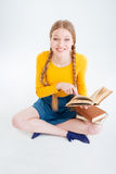 Student sitting on the floor with book Royalty Free Stock Photo