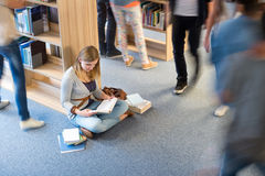 Student sitting floor in library blur motion Royalty Free Stock Photography