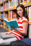 Student sitting on floor in library reading Stock Photography
