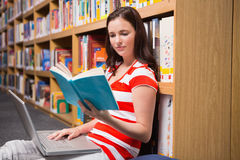 Student sitting on floor in library reading Stock Photo