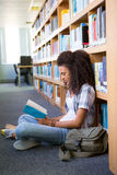 Student sitting on floor in library reading Royalty Free Stock Photo