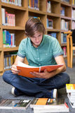 Student sitting on floor in library. At the university Royalty Free Stock Images