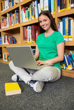 Student sitting on floor in library using laptop Royalty Free Stock Photos