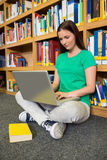 Student sitting on floor in library using laptop Stock Photography