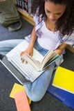 Student sitting on floor in library using laptop Royalty Free Stock Image