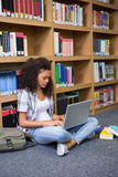 Student sitting on floor in library using laptop Stock Images