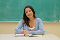 Student sitting in front of the blackboard Royalty Free Stock Images