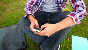 Student sitting on the grass texting on the phone Stock Images
