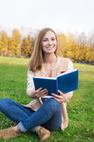 Student sitting on green grass with opened blue book Stock Photos