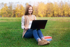 Student sitting on green grass with opened notebook. Lying on the knees. On the sunset royalty free stock photography
